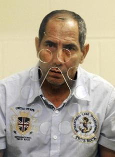 Jose Milthon Freddy Azurdia-Montenegro, 55, of Guatemala, stood behind a partition during his arraignment.
