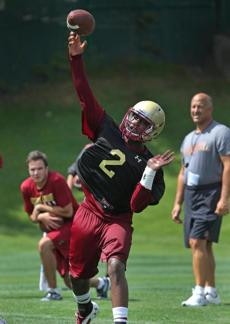 BOSTON, MA - 8/04/2014: ALL IN THE ARM....BC QB Tyler Murphy on the first day of BC football practice on the field with BC coach Steve Addazio looking on in the right background. (David L Ryan/Globe Staff Photo) SECTION: SPORTS TOPIC BC football (1)