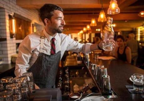 Ryan Connelly wears an apron when he tends bar at Alden & Harlow in Harvard Square.