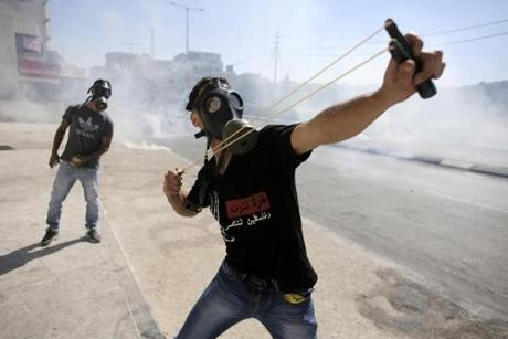 A Palestinian protester with a slingshot lobbed a stone at Israeli troops in Bethlehem on the West Bank.
