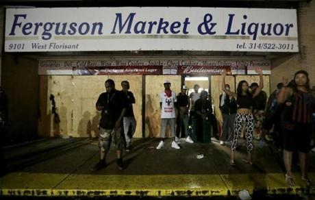 People stood in front of a convenience store in Ferguson after it was looted early Saturday.