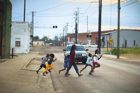 8/9/14 - Greenwood, MS - Destinee Wilson, cq, 14, center, and her family members run across the street during a summer's evening hangout near their housing complex. Topic: 31freedom. Story by Eric Moskowitz/Globe Staff. Dina Rudick/Globe Staff