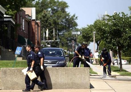 Police officers and firerighters at the scene of a fatal shooting Tuesday in St. Louis.