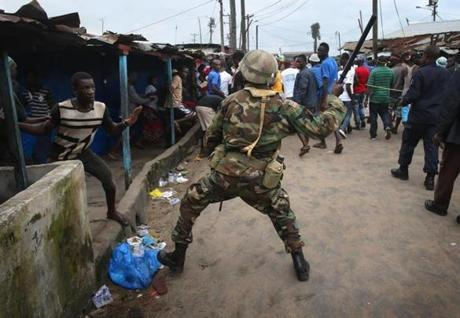 A Liberian Army soldier, part of the Ebola Task Force, beat a local resident while enforcing the quarantine.