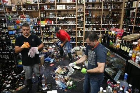 Workers cleaned up bottles that were thrown from the shelves at Van's Liquors in Napa.