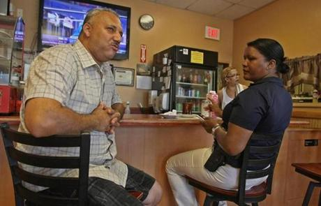 Elisa Fontes, who is from Cape Verde, listened to restaurant owner Jose Cruz at his Sunset Cafe in Brockton