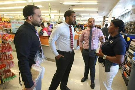 Elisa Fontes talked with store managers Brian Vicente, Jason Barbosa, and Tony Vicente at Vicente's Tropical Supermarket in Brockton