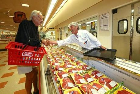 "Chelsea Market Basket meat manager Bob Dietz welcomed back customer Peter Mueller, of Chelsea, on Thursday. ""We're getting it back in motion,"" Deitz said of restocking the store's shelves."