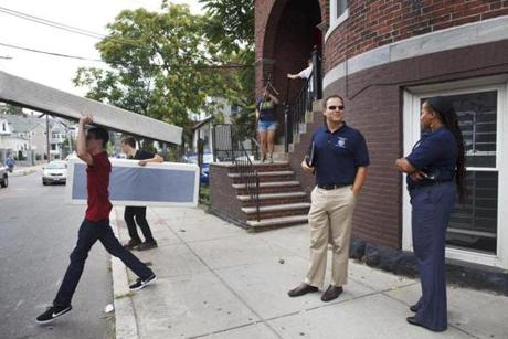 Indira Alvarez, the chief of staff for Boston's Inspectional Services Department, and Ed Coburn, the department's attorney, watched as students hauled furniture in and out of apartments on Linden Street in Allston on Sunday.