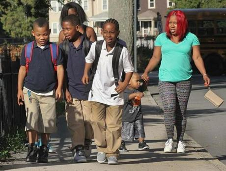 (From left) Third-grader Kamarri McLean, fourth-grader Kamai Buckmire, fifth-grader Anderson Buckmire, Phoenix McLean, and Treasure McLean walked to the entrance of the Edison K-8 School in Brighton, where classes began today.