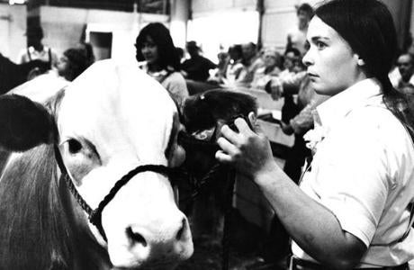 September 18 1979 / fromthearchive / Globe Staff photo by Richard Carpenter / Sally Tator of Rhinebeck, NY solemnly watched the steer auction at Eastern States Exposition. Her steer was next to be auctioned off.