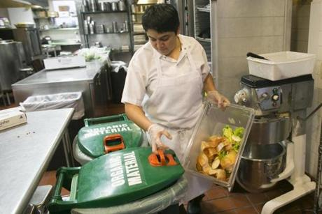August 10, 2014 Boston, MA - City Table at the Lenox Hotel Eliza Martinez dumps compostable waste into an organic waste barrel in the kitchen (Katherine Taylor for The Boston Globe)