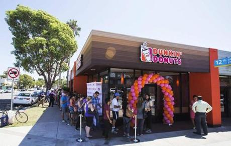 People stand in line outside a newly opened Dunkin' Donuts store in Santa Monica, California September 2, 2014. The store is the first one from the chain to open in the Southern California area. REUTERS/Mario Anzuoni (UNITED STATES - Tags: FOOD BUSINESS)