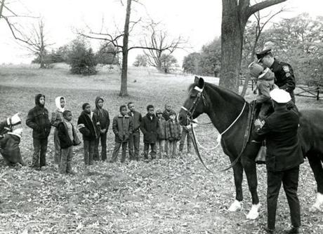November 1 1969 / fromthearchive / Globe Staff photo by Ed Jenner / Victoriz Taylor got a lift up for a ride from Officer Wendall Wallace as a crowd of his friends looked on. On his horse