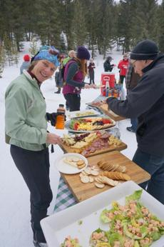 09bigsky - Sue Minter (author's wife) samples some local food during the annual Gorge n' Glide on the cross country ski trails of Lone Mountain Ranch, Big Sky, Montana. (David Goodman)