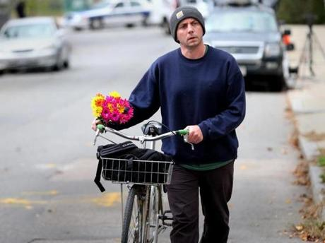 Andrew Burton biked from Roslindale to Hyde Park with a bouquet of flowers to pay his respects.
