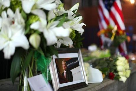 Boston10/31/2014- People waited in line to sign a condolence book in the lobby of Boston City Hall a day after the death of the former Boston mayor Thomas Menino. A photo of him sits on a table with flowers left in the lobby of City Hall. Boston Globe staff photo by John Tlumacki(metro)