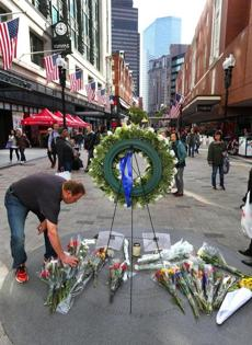 Boston10/31/2014- James Maconochie(cq) leave a bouquet of flowers at a make-shift memorial in downtown crossing a day after the death of the former Boston mayor Thomas Menino. Boston Globe staff photo by John Tlumacki(metro)