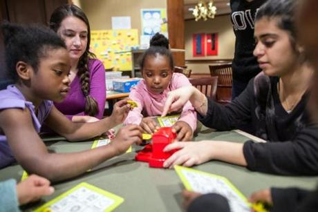 Jaliyah Rogers (center) joins a game with tutors Kendall Fawcett (second from left) and Maram Alarayedh at a Waltham hotel.