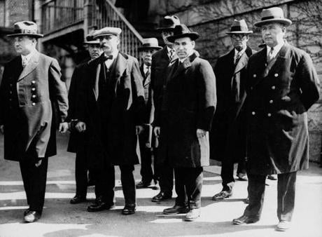 Italian immigrants Nicola Sacco (second from right foreground) and Bartolomeo Vanzetti (second from left foreground) stood in handcuffs with unidentified escorts in Massachusetts around 1927.