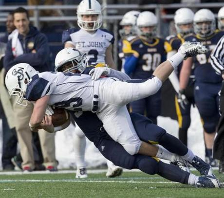 Xaverian's D'Aundre Holmes-Wilfork tackles St. John's Prep's Cody Harwood for a loss.