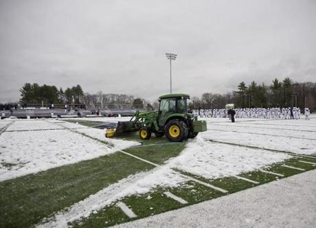 Plowing equiptment on loan from Gillette Stadium removes the snow off the field before Xaverian played St. John's Prep.