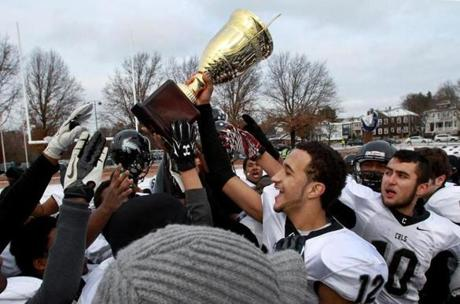 Cambridge players, including quarterback Marcus Collins (holding trophy), celebrate beating Somerville.