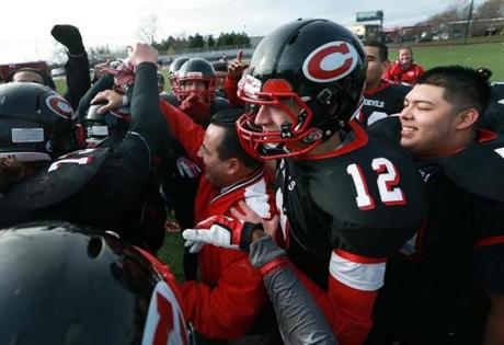 Chelsea head coach Michael Stellato has a big smile and a hug from quarterback Albert Alicea (12) after their victory.