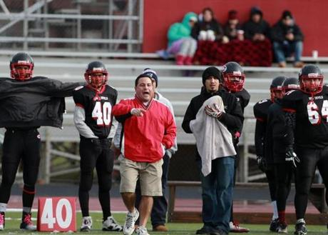 It may be cold enough for a player to be covering up at left, and fans to be bundled under blankets in the stands in the backround, but Chelsea head coach Michael Stellato has his usual shorts on as he patrols the sidelines.