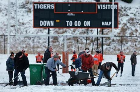 Volunteers work to clear the field of snow at Newton North High School.