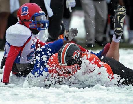 Newton North running back Mike Gately gets a face full of snow as he was brought down by Brookline's Tylen Rose.