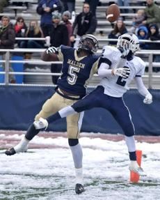 Malden receiver Isaac Bethea (5) battles for the ball with Medford defender Corey Moore (2).
