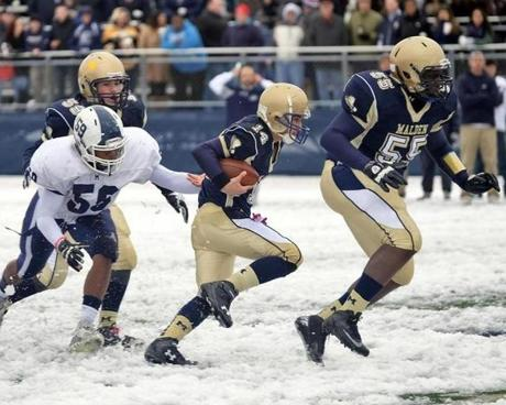 Malden quarterback Andrew Papa (14) gets behind the block of Anthony Boulay (55) as he eludes Medford linebacker Max Tilus (59).