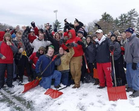 Wakefield head coach Mike Boyages (second from right leaning on shovel) is joined by players, cheerleaders and fans to assist in clearing the snow from the football field.