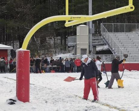 Wakefield head coach Mike Boyages is joined by players, cheerleaders and fans to assist in clearing the snow from the football field.