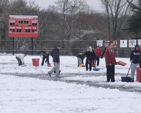 Wakefield High football players, cheerleaders, and fans work to clear the snow from the football field for the Thanksgiving Day game agains Melrose. The game was postponed.