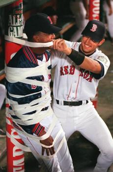 Nomar Garciaparra (right) puts the final touches on wrapping Pedro Martinez to a pole in the dugout during the ninth inning of the Red Sox 6-1 victory over the White Sox on June 25, 1999.