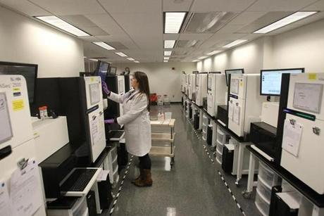 Cambridge, MA., 12/05/14, For Neil Swidey story on the hunt for the ebola virus at the Broad Institute. Kendra West, Process Development Associate at the Broad Institute's Genomics Platform, works with the virus in the lab. She is checking the re-agent pumps in the sequencer. Section: Capitol