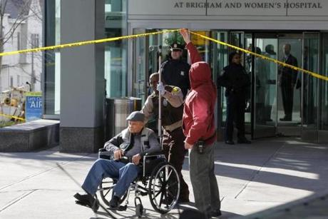 A man in wheelchair was taken away from the building where the shooting occurred.