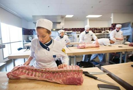 28cheerpix - Patriots cheerleader and Johnson & Wales culinary student LisaMarie Ianuzzi looks over a pork loin during her meat cutting skills class in Providence, Rhode Island, Thursday, Jan. 22, 2015. (Gretchen Ertl for The Boston Globe)