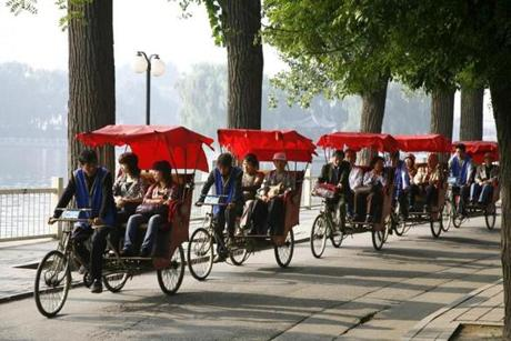 Rickshaw drivers taking tourist on a tour in the Houhai lakes area, Beijing, China.