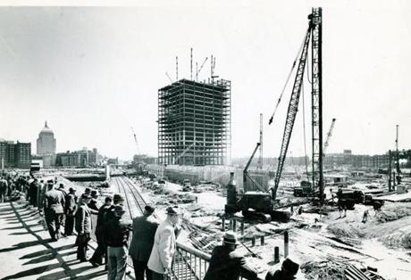 A lunchtime crowd monitored the progress on the Prudential Tower, which would take over bragging rights as the city's tallest building from the John Hancock building (rear left) on its completion in 1964.