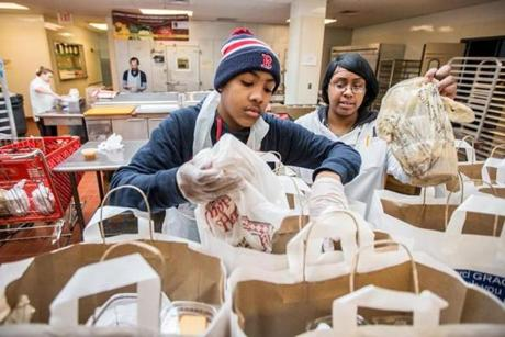 02/20/2015 JAMAICA PLAIN, MA Volunteer Larry Wilkins (cq) 14 (left) and prep cook Lakeisha Hall (cq) build bags for clients at Community Servings (cq) in Jamaica Plain. (Aram Boghosian for The Boston Globe)