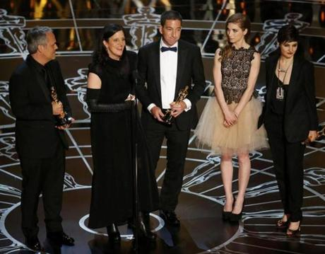 Laura Poitras (second left) spoke after accepting the Oscar along with colleagues for Best Documentary Feature for