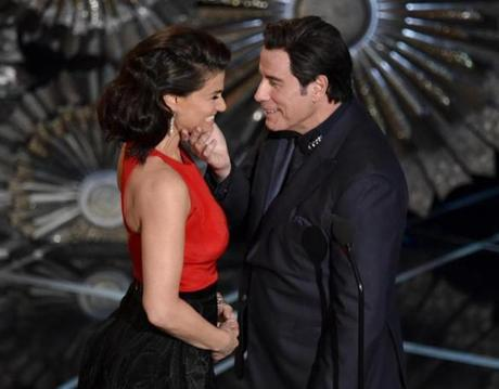 John Travolta (right) touched the face of Idina Menzel as they presented the award for best original song.