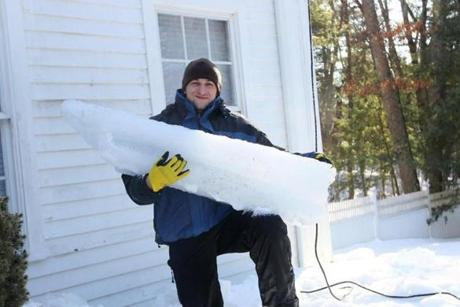 Dmitry Lipinskiy with a giant icicle he was able to knock down from the roof of a Carlisle home using steam.
