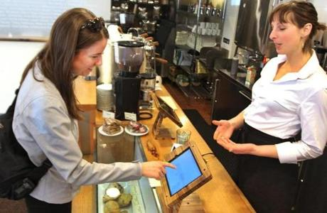 Manager Brittany Lajoie looked on as customer Ailis Tweed-Kent used an iPad to pay for her large latte at Barrington Coffee Roasting Company in Boston.