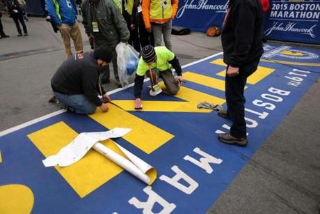 Boston-04/20/15- The Boston Marathon finish line. Workers had to make a repair putting down a new letter N because a truck wheel marred the line. Boston Globe staff photo by John Tlumacki (sports)