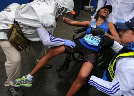 Boston-04/20/15- The Boston Marathon finish line. A runner is helped with a leg cramp as he crossed the finish line. Boston Globe staff photo by John Tlumacki (sports)