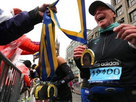 Boston-04/20/15- The Boston Marathon finish line. Dani Armstrong from Grays lake, Ill. gets her medal after crossing the finish.from Boston Globe staff photo by John Tlumacki (sports)